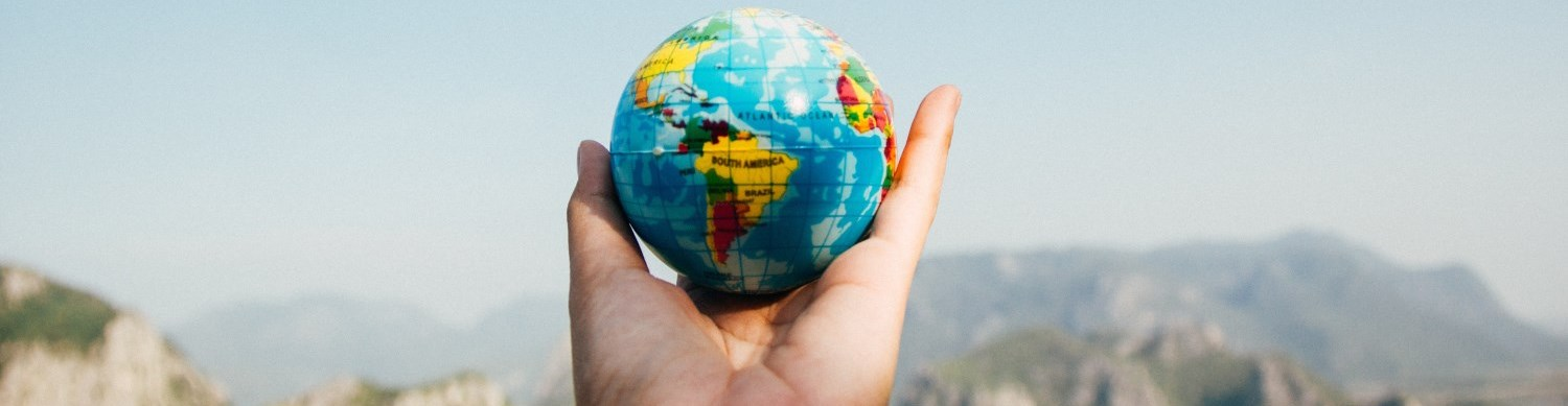 This is a photo of a hand holding a small globe oustide.