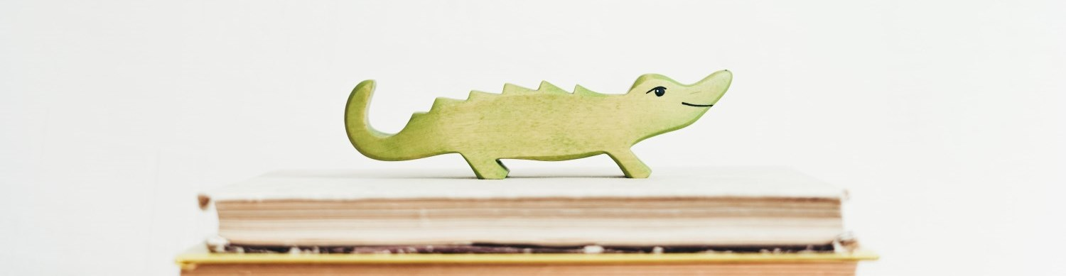 Photo of a toy crocodile on a pile of books